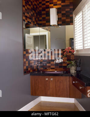 Modern bathroom washbasin set in cupboard unit red brown tiles  interiors bathrooms sinks tiling storage - Stock Photo