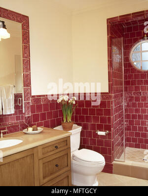 Traditional bathroom red tiles walk in shower washbasin set in cupboard unit toilet interiors bathrooms hot colours showers cubicles - Stock Photo