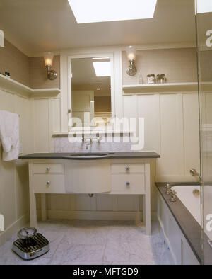 Traditional neutral bathrom panelled walls washbasin set in cupboard unit bath weighing scales  interiors bathrooms sinks baths tiled floor - Stock Photo