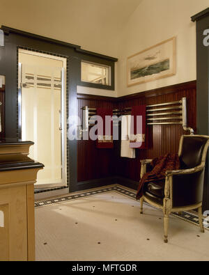 Traditional style bathroom with wood panelled walls and armchair USA - Stock Photo