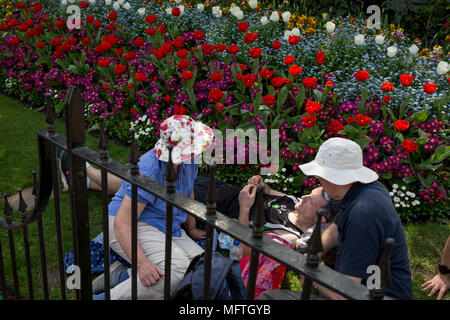 Family sit with a runner who has just finished the London Marathon, in St James's Park, on 22nd April 2018, in London, England. - Stock Photo