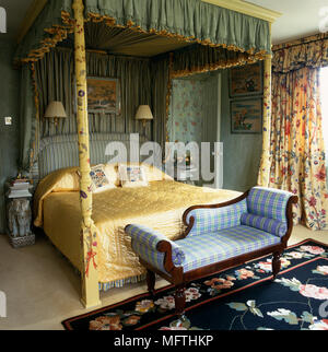 Upholstered chaise longue at the foot of four poster bed with canopy - Stock Photo
