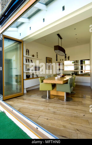 Open plan kitchen diner with wooden floor and doors opening onto patio - Stock Photo
