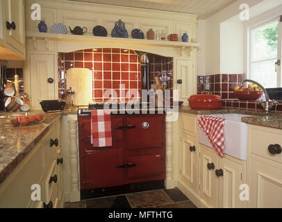Country Style Kitchen With A Large Red Oven And Tiled Flooring Stock