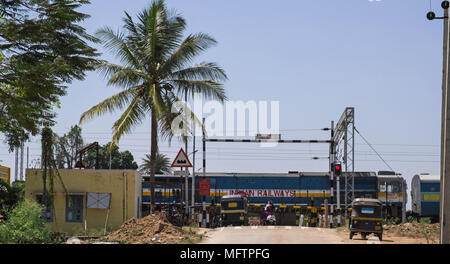 Karnataka, India - March 2, 2018: Passenger train passing over a level crossing in rural area - Stock Photo