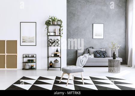 Geometrical carpet in living room interior with metal shelf, sofa, stool, grey wall and paintings - Stock Photo