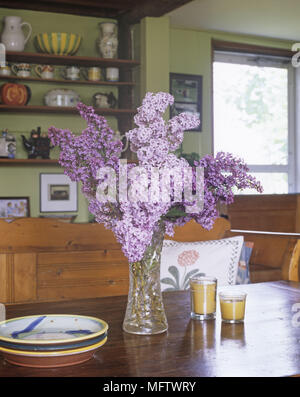Details of a vase of purple flowers on a wooden dining table with a plate and two candles. - Stock Photo