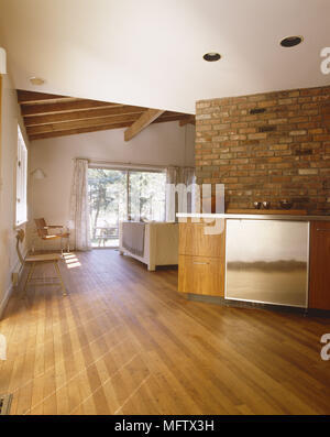 Open plan kitchen leading through to sitting room with wooden flooring and ceiling and bare brick wall - Stock Photo