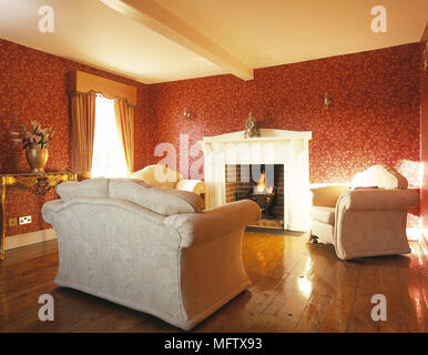 Sofa and armchair in front of fireplace with open fire - Stock Photo