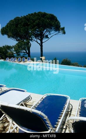 Sun loungers next to infinity pool on hillside. - Stock Photo