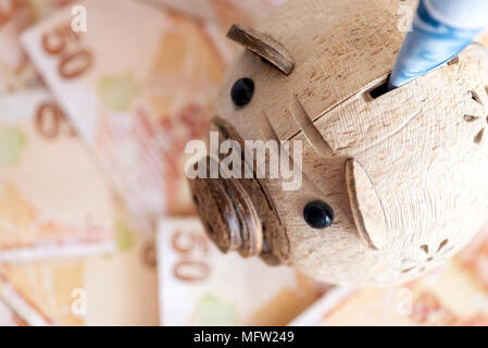 Close-up of turkish currency - high angle view of piggy bank and 50 lira bill banknotes in background - Stock Photo
