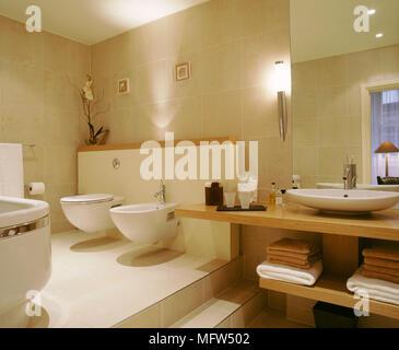 Modern neutral bathroom toilet bidet washbasin on wood unit concealed lighting - Stock Photo