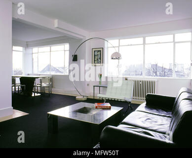 Modern open living area with black carpet dining table and chairs leather sofa curving floor lamp and sunny windows. - Stock Photo
