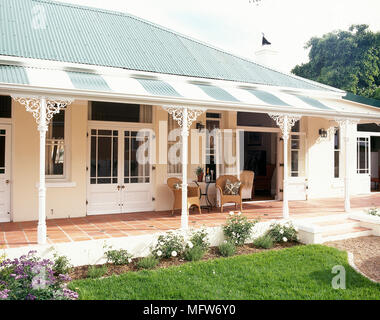Exterior of a bungalow with wicker chairs on a covered veranda. - Stock Photo