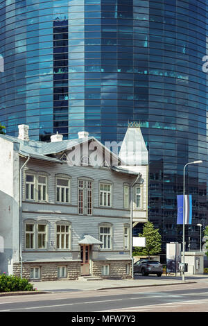 Photo of an old wooden two-storey house against a modern high-rise building of glass and concrete in the Estonian city of Tallinn. - Stock Photo