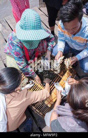 Cham women crab fishers taking crabs out of a traditional Cambodian bamboo crab trap at Kep market in Kampot province - Stock Photo