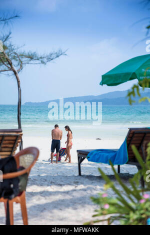 Candid shot of a young couple talking on a white sand beach on an island in Southeast Asia - Stock Photo