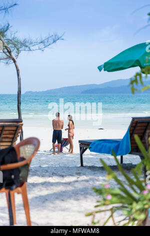 Candid shot of a young couple talking on a white sand beach on an island in Southeast Asia