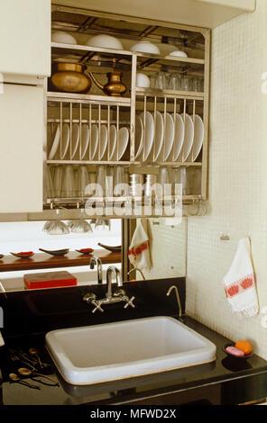 Tableware stored in rack above sink set in shelf unit - Stock Photo