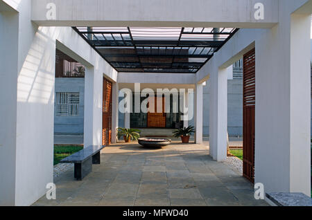 Bench seat on paved area beneath modern structure in garden - Stock Photo