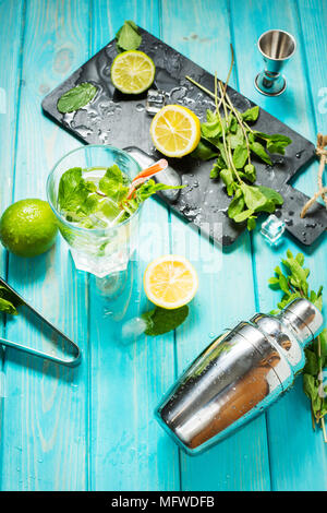 Mojito cocktail with lime and mint in highball glass on a blue wood table. Drink making tools and ingredients for cocktail. - Stock Photo