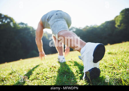 Outdoor cross-country running in summer sunshine concept for exercising, fitness and healthy lifestyle. Close up of feet of a man running in grass - Stock Photo