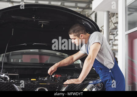 Auto mechanic working in garage. Repair service - Stock Photo
