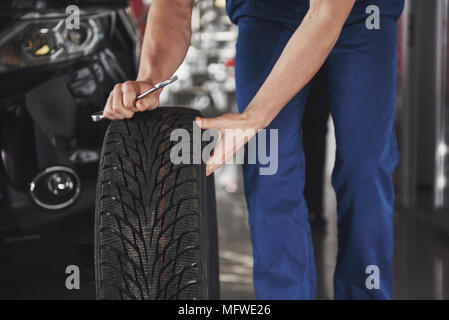Close up of mechanic showing ok gesture with his thumb while holding a wrench - Stock Photo