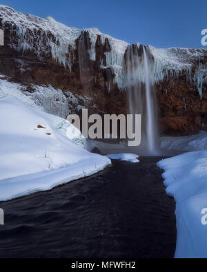 Frozen Seljalandsfoss waterfall in winter in south Iceland - Stock Photo