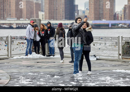 Brooklyn in New York City, tourists take pictures with landmark view of skyline - Stock Photo