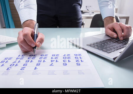 Close-up Of A Businessperson's Hand Marking With Pen On Calendar At Workplace Stock Photo