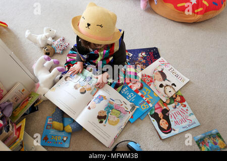 A young girl reading books in her bedroom dressed in cool colourful clothes in London, UK. - Stock Photo
