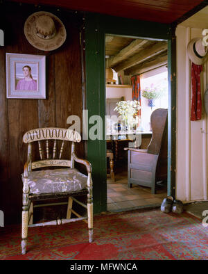 Rustic, country hallway with timber walls, weathered  wood floor, painted craft chair, and an open doorway to an adjacent room. - Stock Photo