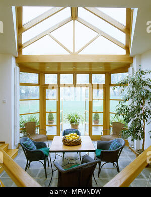 A modern conservatory with a pitched glass roof, dining table with wicker chairs, and a view through open french doors to a grassy lawn. - Stock Photo