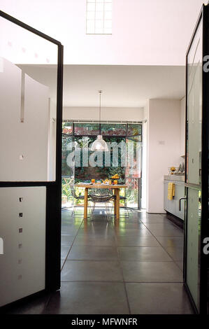 Modern eat-in kitchen with tile floor, open glass doors and a wooden dining table and chairs. - Stock Photo