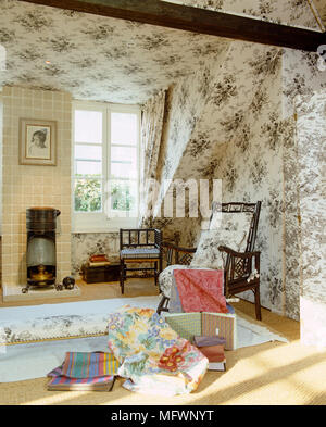 Fabrics in front of wooden chair in sitting room with toile de Jouy pattern wallpaper - Stock Photo