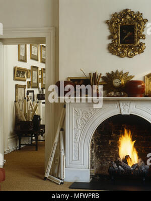 Painting with ornate gold frame mounted above fireplace with mantelpiece full of ornaments next to doorway - Stock Photo