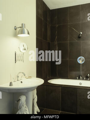Bathroom with slate style tiles on wall above bathtub and next to shaving mirror above wash basin - Stock Photo