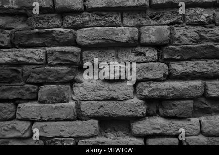 Black and white image of sea salt erosion on brick wall, Venice, Italy. - Stock Photo