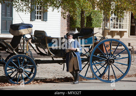 Costumed driver relaxing besides his horse drawn restored carriage on Duke of Gloucester street in colonial Williamsburg Virginia - Stock Photo