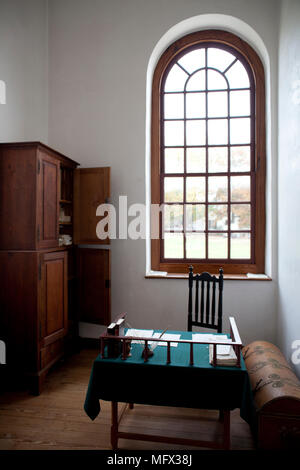 Restored antique office interior in colonial Williamsburg Virginia with writing desk and cupboard - Stock Photo