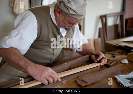 Cabinet maker in authentic early American clothing working in his shop surrounded by his authentic tools in colonial Williamsburg Virginia - Stock Photo