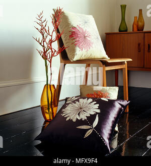 Twig arrangement in glass vase next to wooden chair on black painted floorboards - Stock Photo