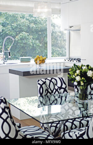 Black and white patterned chairs at glass topped table in modern kitchen - Stock Photo