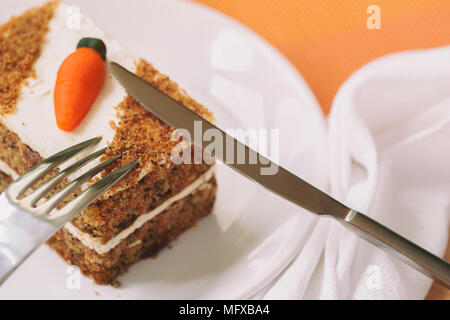 Homemade carrot cake with carrot decorations, slice on white plate close-up, fork, knife, selective focus, copy space - Stock Photo