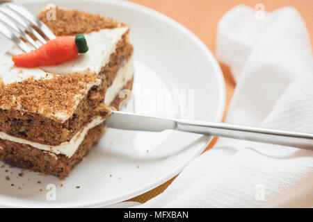 Slice of home made carrot cake, white plate, napkin. Knife cuts an appetizing piece. Sweet healthy vegan food. Selective focus, copy space - Stock Photo