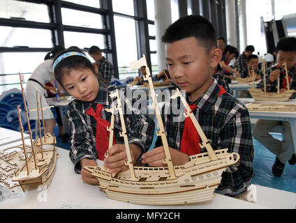 Haikou, China's Hainan Province. 26th Apr, 2018. Pupils make models of ancient merchant ships at China Nanhai (South China Sea) Museum at Tanmen Township in Qionghai City, south China's Hainan Province, April 26, 2018. The museum opened here Thursday. Credit: Zhao Yingquan/Xinhua/Alamy Live News - Stock Photo