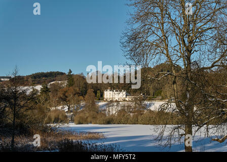 Forneth House, a Private Estate stands out in the low winter Sun overlooking a completely frozen Clunie Loch, near Blairgowrie, Perthshire Scotland. - Stock Photo