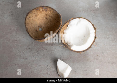 raw organic broken coconut on grey table. Vegetarian food - Stock Photo