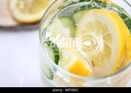 Detox flavored water with lemon and cucumber on white background with wood decoration. Healthy food concept.  Refreshing summer homemade cocktail. - Stock Photo